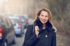 Attraktive stilvolle lächelnde blonde Frau in einer nebelhaften Straße Stockfoto
