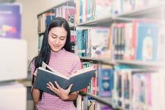 Attraktive Studentenstellung und heben das Buch auf Lizenzfreie Stockbilder