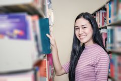 Attraktive Studentenstellung und heben das Buch auf Lizenzfreie Stockfotos