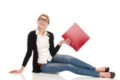 Attraktive Studentin, die auf dem Boden mit Ringmappe sitzt. Lizenzfreie Stockfotografie
