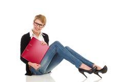 Attraktive Studentin, die auf dem Boden mit Ringmappe sitzt. Stockfotografie