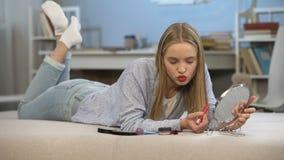 Attraktive Studentin, die im Spiegel, roten Lippenstift vor Datum anwendend aufwirft stock video