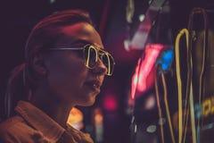 Attraktive styilish Frau wirft f?r Fotografen in den Neonlichtern auf Es gibt Dunkelheit am Hintergrund stockbild