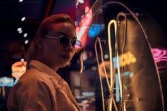 Attraktive styilish Frau wirft f?r Fotografen in den Neonlichtern auf Es gibt Dunkelheit am Hintergrund stockbilder