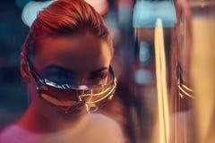 Attraktive styilish Frau wirft f?r Fotografen in den Neonlichtern auf Es gibt Dunkelheit am Hintergrund stockfoto