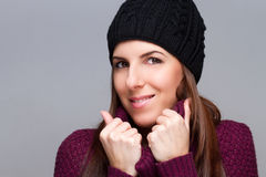 Attraktive tragende Kappe der jungen Frau und Lächeln auf hellem Hintergrund lizenzfreie stockfotos