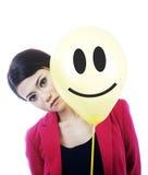 Attraktive traurige Geschäftsfrau hinter einem smileygesicht Stockfoto