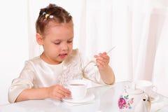 Attraktive trinkende Tasse Tee des kleinen Mädchens Stockfotos