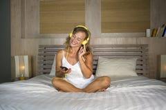 Attraktive und glückliche kaukasische blonde Frau 30s im Bett ist zu Hause Lizenzfreie Stockbilder