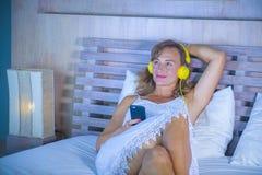 Attraktive und glückliche kaukasische blonde Frau 30s im Bett ist zu Hause Lizenzfreies Stockbild