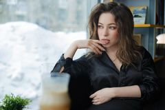 Attraktive und nette junge Frau, die im Caf? l?chelt stockfotos