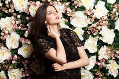 Attraktive und sinnliche Frau auf Blumenwand im Studiofoto stockfotografie