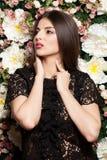 Attraktive und sinnliche Frau auf Blumenwand im Studiofoto stockbilder
