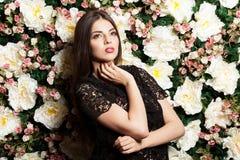 Attraktive und sinnliche Frau auf Blumenwand im Studiofoto stockfotos