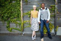Attraktive und stilvolle multikulturelle Paare im Liebeshändchenhalten durch einen Zaun in einer Efeu-gefüllten städtischen Lands Lizenzfreies Stockbild