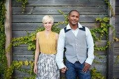 Attraktive und stilvolle multikulturelle Paare im Liebeshändchenhalten durch einen Zaun in einer Efeu-gefüllten städtischen Lands Stockbild