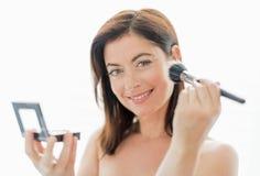 Attraktive Vierzigerin, die Make-up anwendet stockbilder