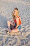 Attraktive weibliche Aufstellung für die Kamera, die auf dem Sand sitzt Lizenzfreie Stockbilder
