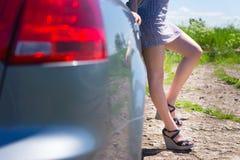 Attraktive weibliche Beine nahe dem Auto stockfoto
