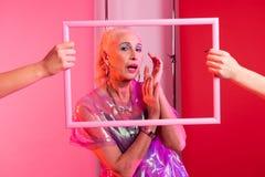 Attraktive weibliche Person, die durch weißen Rahmen schaut stockfoto