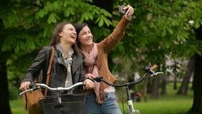Attraktive weibliche Radfahrer fotografieren sich unter Verwendung Smartphones draußen im Park während der Frühlings-Zeit Zwei stock video