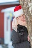 Attraktive Weihnachtsfrau mit Weihnachtsmann-Hut Stockfotografie