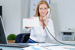 Attraktive woman in office at telephone shows  banner. Attraktive woman in office at telephone shows blank banner Stock Photo
