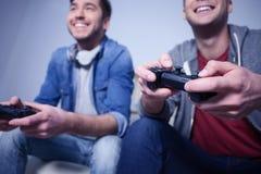 Attraktive zwei Kerle spielen Videospiele stockbild