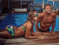Attraktiven Paare, ein hübscher muskulöser Mann und eine sexy Frau, die nahe dem Pool nachdem dem Schwimmen sich entspannen Genie lizenzfreie stockfotografie