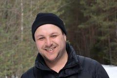 Attraktiven vierzig etwas Mann mit dem langen gelockten Haar wirft für ein Foto während heraus für einen Weg im Wald im Winter au stockbilder