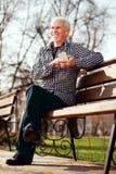 Attraktiver älterer Mann, der Entscheidung über Lied trifft stockbild