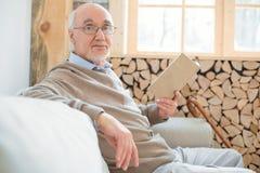 Attraktiver älterer Mann, der in Lesung mit einbezieht lizenzfreie stockbilder