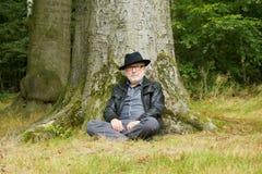 Attraktiver älterer Mann, der unter Baum sitzt Lizenzfreie Stockbilder