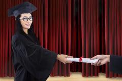 Attraktiver Absolvent gegebenes Zertifikat auf Stadium Stockfotografie