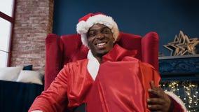 Attraktiver afrikanischer Mann in Weihnachtsmann-Kostüm und -hut, die das Geschenk beim Sitzen im Stuhl nahe Weihnachtsbaum halte stock footage