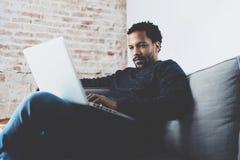 Attraktiver bärtiger afrikanischer Mann, der an Laptop beim Sitzen des Sofas in seinem modernen Innenministerium arbeitet Konzept stockfoto