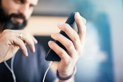 Attraktiver bärtiger Kerl, der zufälliges graues T-Shirt hörende Musik in den Kopfhörern, soziale Netzwerke auf Smartphone überpr lizenzfreies stockbild