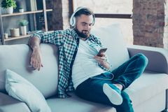Attraktiver, bärtiger Mann, der auf dem Sofa im Wohnzimmer, Bein sitzt Lizenzfreies Stockfoto