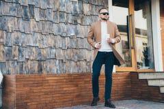 Attraktiver bärtiger Mann, der im braunen Mantel, in der Sonnenbrille und im Tasse Kaffee in seinen Händen stehen Caféhintergrund lizenzfreie stockbilder