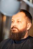 Attraktiver bärtiger Mann in einem Friseursalon Stockbild