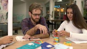 Attraktiver bärtiger Mann mit Gläsern und eine nette Freundin mit dem langen dunklen Haar errichten einen Turm von mehrfarbigem stock video footage