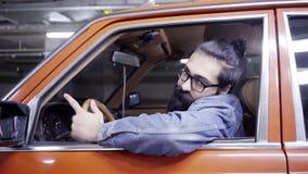 Attraktiver bärtiger Mann mit langen Haarblicken aus Autofenster und -antrieben heraus weg stock footage