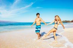 Attraktiver Betrieb und Spielen des glücklichen Paars Lizenzfreie Stockfotografie