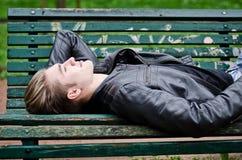 Attraktiver blauäugiger, blonder junger Mann, der auf Parkbank legt Lizenzfreie Stockfotografie