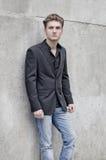 Attraktiver blauäugiger, blonder junger Mann, der an der weißen Wand sich lehnt Lizenzfreie Stockfotos