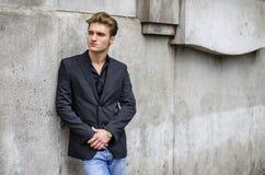 Attraktiver blauäugiger, blonder junger Mann, der an der weißen Wand sich lehnt Stockbilder