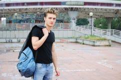 Attraktiver blauäugiger, blonder junger Mann mit ruck Sack draußen Stockfoto
