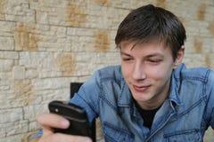 Attraktiver blaue Augen-blonder Mann, der Telefon überprüft Lizenzfreies Stockfoto