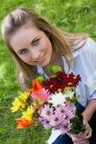Attraktiver blonder Jugendlicher, der einen schönen Blumenstrauß anhält Lizenzfreie Stockfotografie