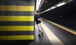 Attraktiver blonder junger Mann in der Bahnstation unter Verwendung des Mobiltelefons Lizenzfreie Stockbilder